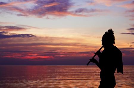 silhouette umana che suona il flauto al tramonto