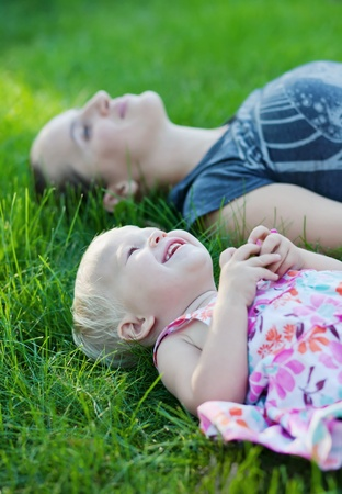 Mother and her baby lying on the grass photo