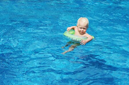 Baby swimming in the blue pool water Stock Photo