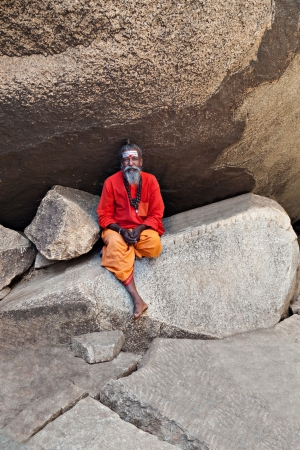 HAMPI, INDIA - JULY 26: Sadhu sitting in the cave at July 26, 2012 in Hampi, India. Sadhus are holy men who have chosen to live an ascetic life and focus on the spiritual practice of Hinduism. Stock Photo - 15547309