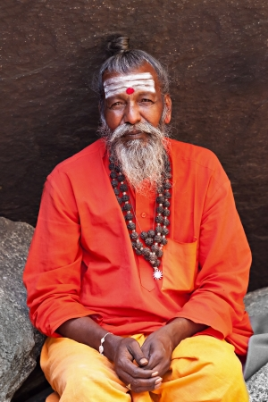 HAMPI, INDIA - JULY 26: Sadhu sitting in the cave at July 26, 2012 in Hampi, India. Sadhus are holy men who have chosen to live an ascetic life and focus on the spiritual practice of Hinduism. Stock Photo - 15546986
