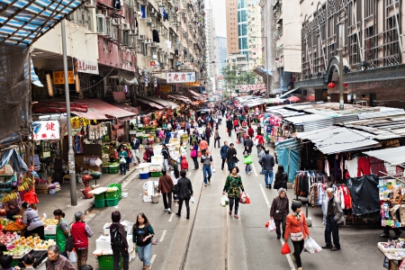 HONG KONG - FEBRUARY 21 : Street market in Central district on February 21, 2013 in Hong Kong. People buying and selling fruit, meat, fish and vegetable between buildings in Central district.  Stock Photo - 22053417