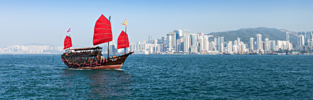 HONG KONG - FEBRUARY 21: The junk boat provides the harbor tour on February 21, 2013 in Hong Kong. A red chinese traditional junk boat, Aqua Luna, is one of famous tourist attraction.