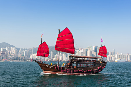 HONG KONG - FEBRUARY 21: The junk boat provides the harbor tour on February 21, 2013 in Hong Kong. A red chinese traditional junk boat, Aqua Luna, is one of famous tourist attractive.