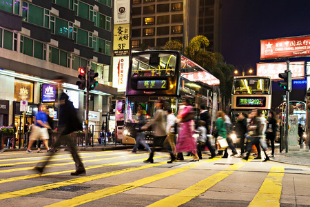 HONG KONG - FEBRUARY 21: Unidentified people crossing the street on February 21, 2013 in Hong Kong. With a 7 million people, Hong Kong is one of the most densely populated areas in the world