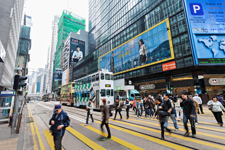 HONG KONG - FEBRUARY 21: Unidentified people crossing the street on February 21, 2013 in Hong Kong. With a 7 million people, Hong Kong is one of the most densely populated areas in the world.