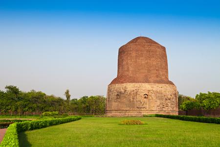 Dhamekh Stupa on green grass in Sarnath, India