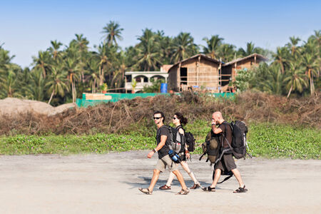 GOA, INDIA - NOVEMBER 08: Backpackers walking on the Goa beach on November 08, 2011 in Goa, India. Goa is a very popular beach place to go for backpackers and also for more upmarket travelers.
