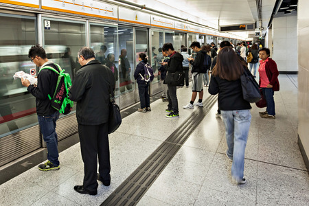 HONG KONG - FEBRUARY 23: Subway station interior on February 23, 2013 in Hong Kong. Over 90% daily travelers use public transport. Its the highest rank in the world. Focus on left passanger.