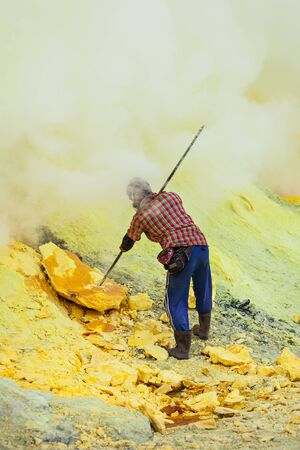 Sulfur miner inside crater of Ijen volcano, East Java, Indonesia Stock Photo
