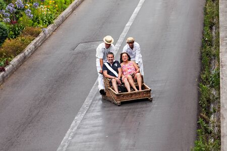 toboggan: FUNCHAL, MADEIRA - JuLY 04: Traditional downhill sledge trip on July 04, 2014 in Madeira, Portugal. Sledges were used as local transport, currently these Toboggan riders are a touristic attraction.
