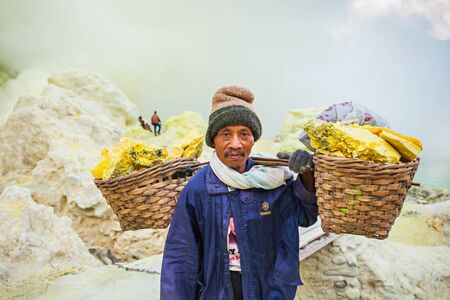 BANYUWANGI, INDONESIA - OCTOBER 27, 2014: Unidentified Sulfur miner inside crater of Ijen volcano, East Java, Indonesia.