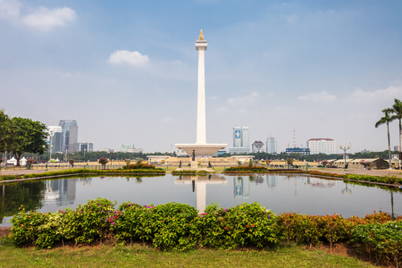 squares: JAKARTA, INDONESIA - OCTOBER 21, 2014: The National Monument is a 132m tower in the centre of Merdeka Square, Jakarta, symbolizing the fight  for Indonesia.
