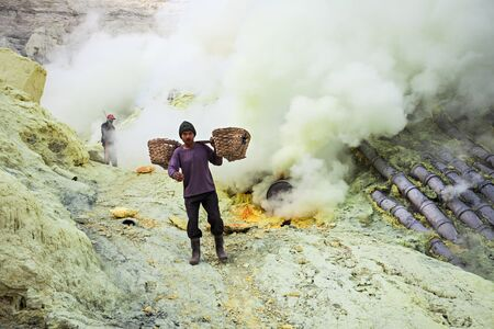 sulfur: BANYUWANGI, INDONESIA - OCTOBER 27, 2014: Unidentified Sulfur miners inside crater Ijen volcano crater, Banyuwangi district, Indonesia. Editorial