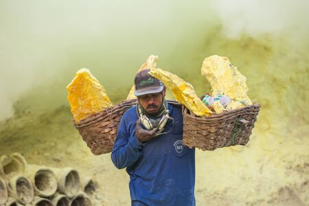 BANYUWANGI, INDONESIA - OCTOBER 27, 2014: Unidentified Sulfur miner inside crater of Ijen volcano, East Java, Indonesia.
