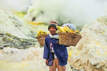 sulfur: BANYUWANGI, INDONESIA - OCTOBER 27, 2014: Unidentified Sulfur miner inside crater of Ijen volcano, East Java, Indonesia.