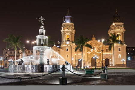 people in church: The Basilica Cathedral of Lima at night, it is a Roman Catholic cathedral located in the Plaza Mayor in Lima, Peru