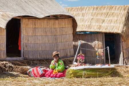 quechua indian: PUNO, PERU - MAY 14, 2015: Unidentified woman in traditional dress showing handicrafts in Uros Island.