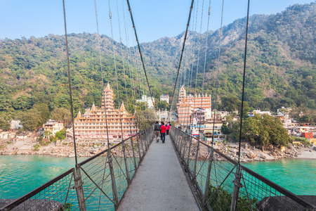 ancient yoga: RISHIKESH, INDIA - NOVEMBER 12, 2015: Lakshman Jhula is an iron suspension bridge situated in Rishikesh, Uttarakhand state of India. Editorial