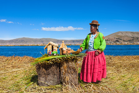 quechua: PUNO, PERU - MAY 14, 2015: Unidentified woman in traditional dress showing handicrafts in Uros Island.