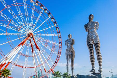 metal sculpture: BATUMI, GEORGIA - SEPTEMBER 22, 2015: Moving metal sculpture Ali and Nino (old name Man and Woman) by Tamara Kvesitadze and Ferris wheel in Batumi, Georgia. Editorial