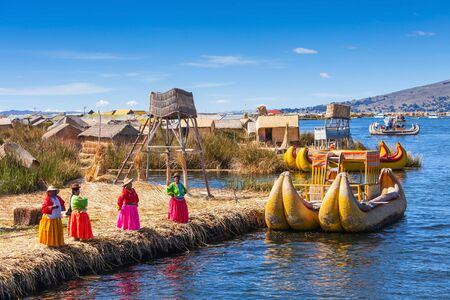 quechua: PUNO, PERU - MAY 14, 2015: Unidentified women in traditional dresses welcome tourists in Uros Island. Editorial