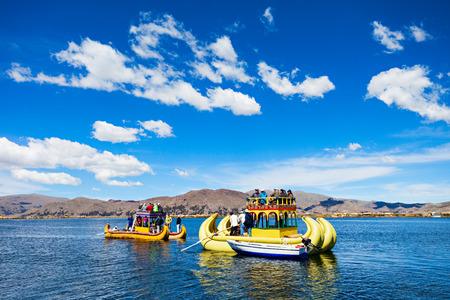 quechua indian: PUNO, PERU - MAY 14, 2015: Unidentified tourists in Totora boat, Titicaca lake near Puno, Peru Editorial