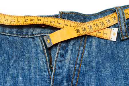 decreasing in size: measuring tape around womans trousers
