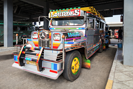 taxi famous building: MANILA, PHILIPPINES - FEBRUARY 26: Jeepney on the bus station on February, 26, 2013, Manila, Philippines. Jeepney is a most popular public transport on Philippines. Editorial