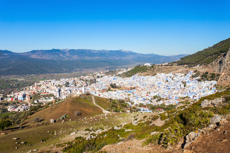 noted: Chefchaouen and Rif mountains aerial panoramic view, Morocco. Chefchaouen is a city in northwest Morocco. Chefchaouen is noted for its buildings in shades of blue.