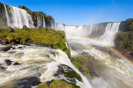Rainbow and Iguazu Falls. Iguazu Falls are waterfalls of the Iguazu River on the border of the Argentina and the Brazil. Stock Photo