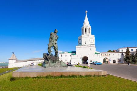 KAZAN, RUSSIA - JUNE 30, 2016: Musa Mostafa Dzhalil Monument and Spasskaya (Saviors) Tower, Kazan Kremlin in Russia. Spasskaya Tower serves as Kremlin main entrance.