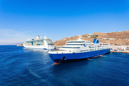 Cruise ship and ferry boat near the Mykonos island, Cyclades in Greece. Stock Photo