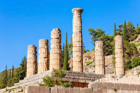 consulted: Ruined columns of the Temple of Apollo in Delphi. Delphi is ancient sanctuary that grew rich as seat of oracle that was consulted on important decisions throughout the ancient classical world. Stock Photo