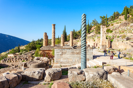 delphi: Serpent Column of Plataea and Temple of Apollo in Delphi. Delphi is ancient sanctuary that grew rich as seat of oracle that was consulted on important decisions throughout ancient classical world. Stock Photo