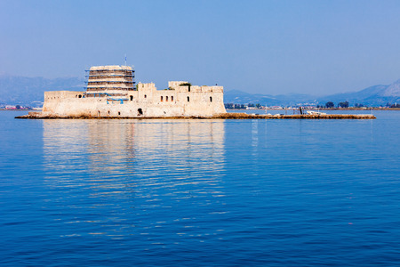 Bourtzi is a water castle located in the middle of Nafplio harbour. Nafplio is a seaport town in the Peloponnese peninsula in Greece. Editorial