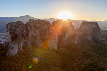 The Meteora at sunset. Meteora is a formation of immense monolithic pillars and hills like huge rounded boulders which dominate the local area.