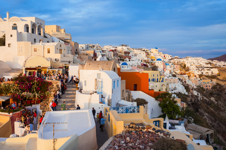Oia town aerial panoramic view on sunset. Oia or Ia is a small town on Santorini island in the Cyclades, Greece.