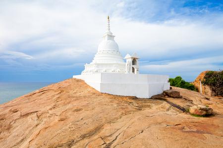 Kirinda Viharaya Temple Stupa near Tissamaharama city, Sri Lanka. Kirinda is a buddhist temple built on the huge rock boulder on Kirinda beach. Stock Photo