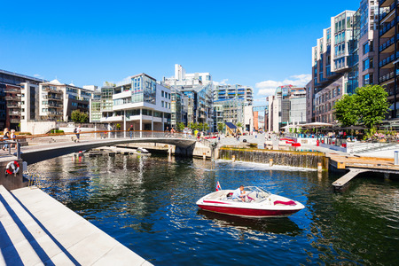 OSLO, NORWAY - JULY 20, 2017: Bridge through canal at the Aker Brygge neighbourhood in Oslo, Norway. Aker Brygge is a popular area for shopping, 