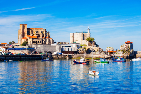 Boats at the port of Castro Urdiales, Santa Maria Church and Santa Ana Castle Lighthouse in Cantabria region in northern Spain. Stock Photo