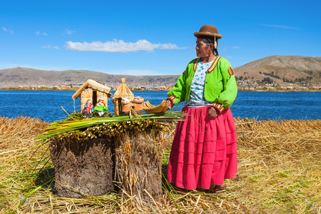 PUNO, PERU - MAY 14, 2015: Unidentified woman in traditional dress showing handicrafts in Uros Island.