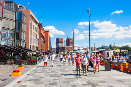 OSLO, NORWAY - JULY 20, 2017: Pedestrian promenade at the Aker Brygge waterfront in Oslo, Norway. Aker Brygge is a popular area for shopping, dining, and entertainment. Редакционное