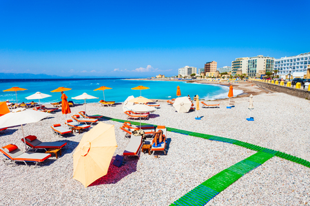 Sunbeds with umbrellas at the Rhodes city beach in Rhodes island in Greece