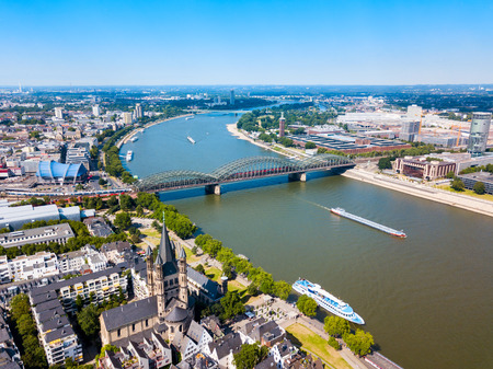 Great Saint Martin Church and Hohenzollern Bridge through Rhine river in Cologne, Germany