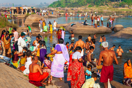 HAMPI, INDIA - FEBRUARY 20, 2012: Indian people bathing and washing their clothes in the river in India
