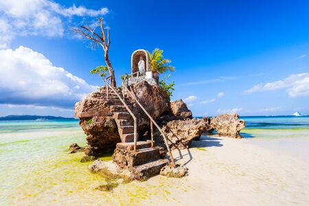 Willys Rock is a tidal island with a statue of the Virgin Mary at the Boracay beach in Philippines Stock Photo