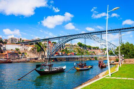 Traditional boats with porto wine barrels at Douro river and Dom Luis I Bridge in Porto city, Portugal