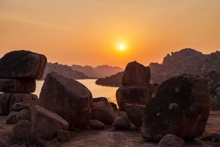 Mountain with boulders and river at Hampi, the centre of the Hindu Vijayanagara Empire in Karnataka state in India