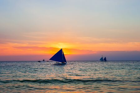 Traditional filipino boat at the idyllic white sand beach at Boracay island in Philiphines at sunset Stockfoto